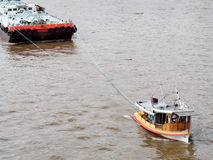 Tug boat service on CHAO  PHRAYA river BANGKOK, THAILAND pulling heavy floating container Royalty Free Stock Image