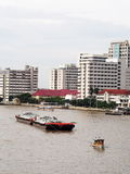Tug boat service on CHAO  PHRAYA river BANGKOK, THAILAND pulling heavy floating container. Slowly along river traffic , Photo from walkway of The PHRA PIN-KLAO Royalty Free Stock Photography