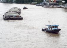 Tug boat service on CHAO  PHRAYA river BANGKOK, THAILAND pulling heavy floating container. Slowly along river traffic , Photo from walkway of The PHRA PIN-KLAO Royalty Free Stock Image