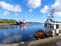 Tug boat and freighters. Bright beautiful day by the Atlantic ocean, with the vessels around Stock Photos