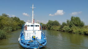 Tug boat on a small delta canal. A civilian tug boat on a small canal in the Danube Delta in a sunny day Royalty Free Stock Photography