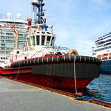 Tug boat. A small tugboat and two huge cruise ships on the quayside in a harbour Stock Photography