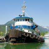 A tug-boat tied alongside a dock in alaska Stock Photo