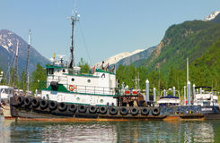 A tug-boat tied alongside a dock in alaska Royalty Free Stock Photography