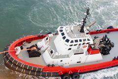 Tug Boat tow line attached to ship to maneuver the mooring/docking process. Small red and white powerful vessel stock photo
