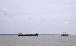 Tug boat is towing barge Stock Images