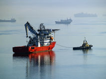 Tug boat towing supply vessel. Stock Image