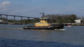 Tug boat travels on Savannah river on a sunny day stock footage
