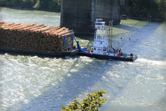 Tug boat under Bridge. A tug boat pushing a load of logs down the river under a bridge. Shallow depth of field Stock Images