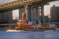 Tug boat under Brooklyn Bridge, New York NY Stock Image