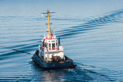 Tug boat with white superstructure underway. Pulling the rope, rear view Royalty Free Stock Photography