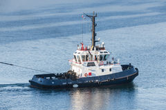 Tug boat with white superstructure underway. Pulling the rope, side view Royalty Free Stock Photos