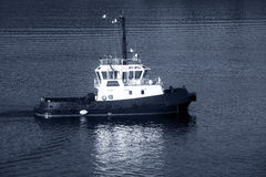 Tug boat with white superstructure underway, side view, monochro Royalty Free Stock Photos