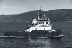 Tug boat with white superstructure. Underway, side view. Trondheim, Norway. Monochrome photo Royalty Free Stock Photo