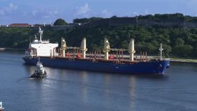 Tug Boats Guide Freighter Ship in Havana Port in Kuba stock video footage