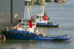 Tug boats pushing a cargo ship to port. Tug boats pushing a cargo ship Stock Image