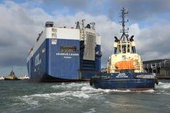 Tug and cargo ship Stock Photos