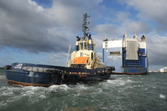 Tug and cargo vessel Stock Images