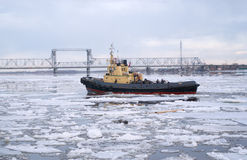 Tug and driving of ice on river Royalty Free Stock Photo