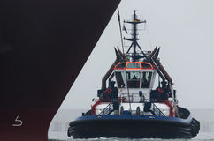 TUG AND GAS TAKER. The tug  maneuver at the bow of a large ship Royalty Free Stock Photos