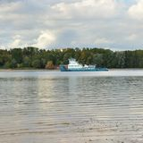 The tug goes on the river. The tug goes along the Sheksna River from the Rybinsk Reservoir. Water. Waves. Blue sky. clouds Royalty Free Stock Images