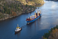 Tug hebert are towing bbc europe out of the fjord. When it comes so large ships as bbc europe in ringdalsfjord they must have towing assistance to get out to the Stock Photos