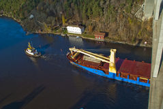 Tug hebert are towing bbc europe out of the fjord Stock Photo