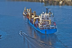 Tug herbert are towing bbc europe out of the fjord. When it comes so large ships as bbc europe in ringdalsfjord they must have towing assistance to get out to Stock Image