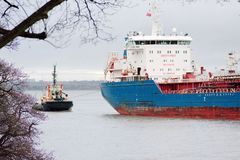 A Tug Holding The line for an Oil Tanker Pulled Shore-ward By The Flowing Tide stock image