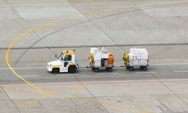 Tug and luggage on the airport Stock Photos