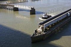 Tug Manoevers Through Swing Bridge. A tug boat manoevers between a swinging train trestle Stock Image