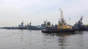 The tug with military sailors on the background of the ships of the Baltic fleet. Preparation for Navy Day in Kronstadt. SAINT PETERSBURG, RUSSIA - JULY 29, 2017 stock footage