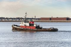 Tug Morgan on Acushnet River. New Bedford, Massachusetts, USA - January 25, 2019: Tug Morgan heading down river with New Bedford residential neighborhood in royalty free stock image