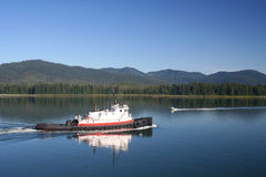 Tug Passing Speedboat. A tug boat passes a speedboat while traversing the Wrangell Narrows, near Wrangell, Alaska stock photos