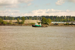 A tug pulling cargo up the fraser river in canada Stock Image