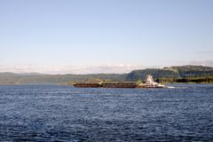 The tug pushes two coupled barges along the wide Columbia River Stock Photo