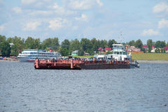 The tug River 76 with a barge floats on the river Volga. City ferry in Myshkin Royalty Free Stock Image