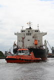 Tug and ship Stock Images
