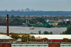 Tug ship moving past the cargo port Stock Images