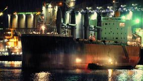 Tug And Ship Near Refinery. Tug guiding large oil tanker into dock by refinery at night in heavy rain stock footage