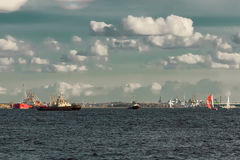 Tug ships and sailboats. Against cargo terminal in Riga stock photos