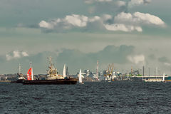 Tug ships and sailboats. Against cargo terminal in Riga Royalty Free Stock Photo