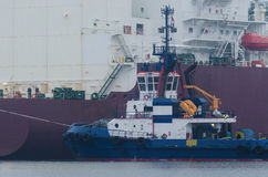 TUG AT THE STERN OF LNG CARRIER Royalty Free Stock Photos