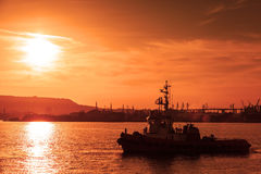Tug is underway on Black sea at sunset Stock Images