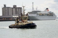 Tug underway and cruise ship berthed Royalty Free Stock Photos