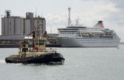 Tug underway with a cruise ship Southampton Docks Stock Images