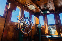 Tug Vessel Deck Command Wheel. Tug vessels small wooden deck command room with wooden steering wheel and signal gauges to engine room from pilot captain Stock Photo