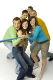 Tug of war. Group of 6 happy teenagers pulling the rope. They're looking at camera. White background Royalty Free Stock Photos