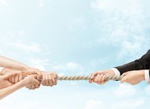 Tug of war. Arious hands during tug war on sky backgrounds stock photos