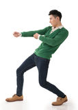 Tug of war. Asian young man posing tug of war, full length portrait isolated on white stock photos